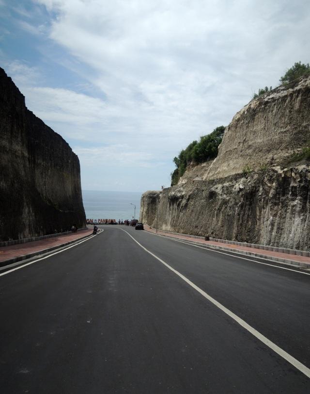 Diapit dua bukit batu. Ohya dulunya, jalan menuju pantai rahasia ini merupakan bekas pertambangan batu.